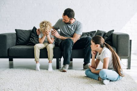 two sad preteen children and father having conflict Stock Photo