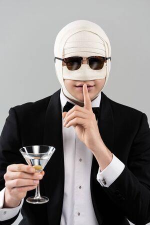 Front view of man in formal wear and sunglasses with elastic bandage on head holding glass of cocktail and showing hush sign isolated on grey background