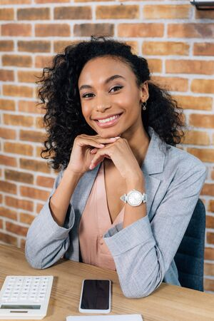 Smiling African American Casual businesswoman propping chin in loft office