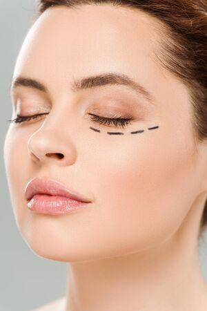 Nahaufnahme einer schönen Frau mit geschlossenen Augen und Flecken im Gesicht isoliert auf grauem Hintergrund