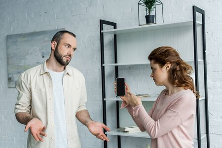 offended woman pointing with finger at smartphone with blank screen near man at home