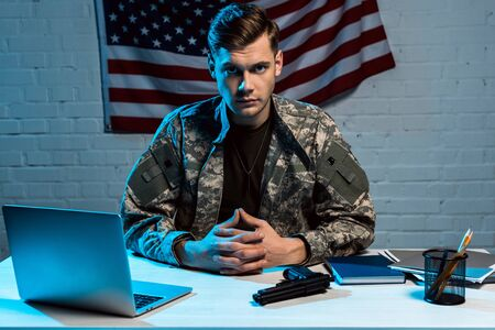 handsome military man in uniform sitting in office and looking at camera