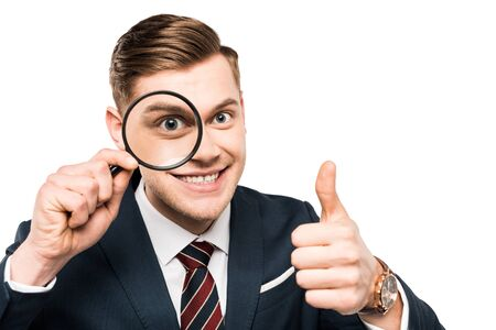 cheerful businessman showing thumb up and holding magnifying glass near eye isolated on white