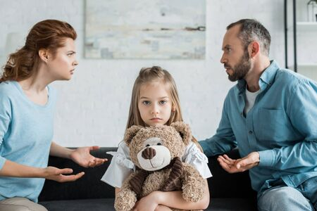 selective focus of upset kid holding teddy bear near quarreling parents
