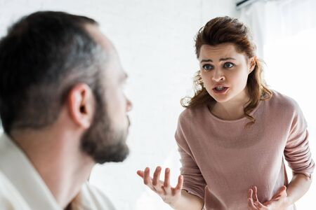 selective focus of offended woman gesturing while looking at man Stock Photo