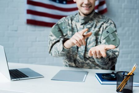 cropped view of happy man in military uniform pointing with finger in office
