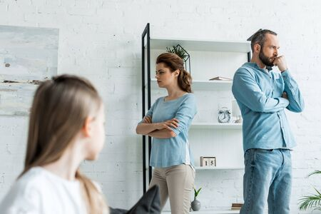 selective focus of offended woman standing with crossed arms near husband at home