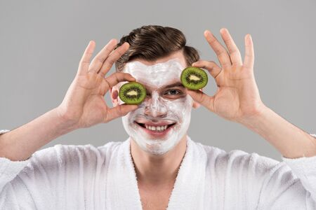 Front view of smiling man in bathrobe holding cut kiwi isolated on grey background 免版税图像