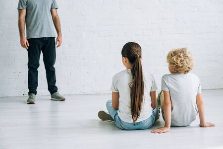 partial view of abusive father and sad kids sitting on floor