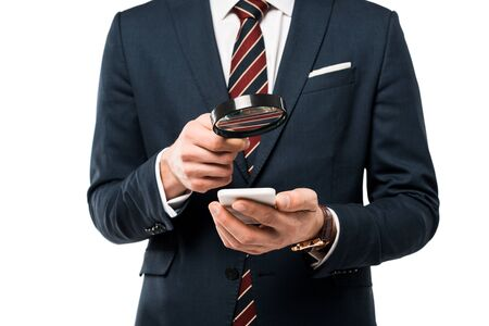 cropped view of businessman holding magnifying glass near smartphone isolated on white
