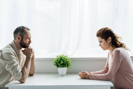 handsome bearded man and upset and attractive woman after quarreling at home Stock Photo