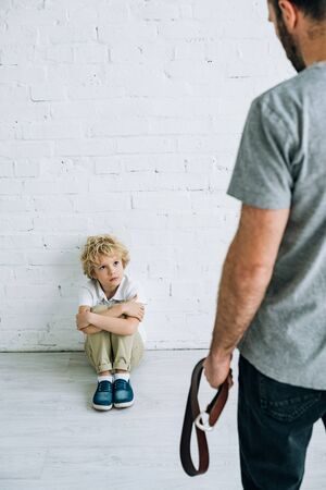 cropped view of father holding belt and sad son sitting on floor Stock Photo