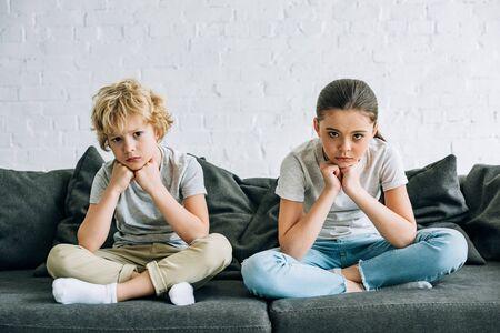 Twee trieste kinderen zitten op de bank in de woonkamer