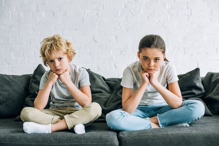Two sad kids sitting on sofa in living room