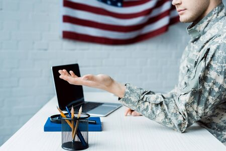 cropped view of soldier gesturing near laptop with blank screen