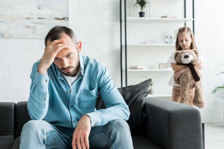 selective focus of upset man sitting on sofa near daughter at home