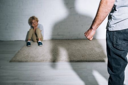 partial view of abusive father and scared son sitting on carpet Stock Photo