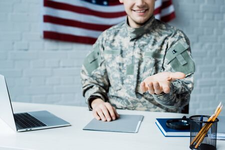 cropped view of happy soldier gesturing near laptop in office Фото со стока