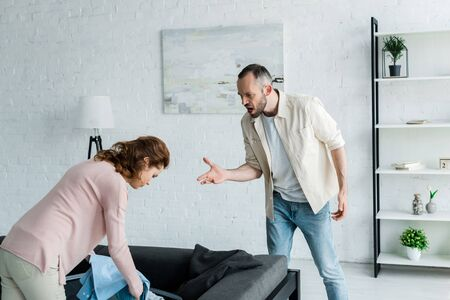 angry man gesturing while looking at woman packing clothes at home