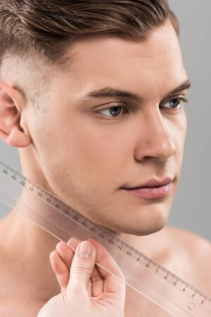 partial view of plastic surgeon measuring face with ruler isolated on grey Фото со стока