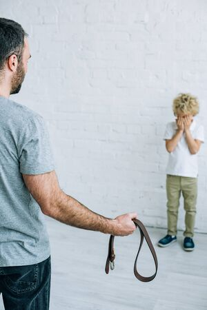 cropped view of father with belt and crying son at home Stock Photo