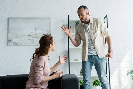 angry man gesturing while looking at wife sitting on sofa at home Stock Photo