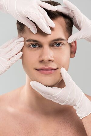Partial view of cosmetologists in latex gloves touching face isolated on grey background