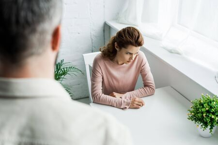 selective focus of upset brunette woman sitting near man at home