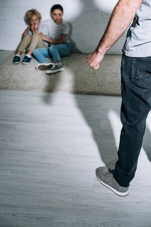 cropped view of father and scared children sitting on carpet Stock Photo