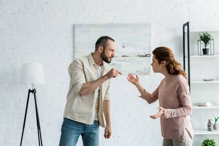 bearded man standing and pointing with finger at attractive woman