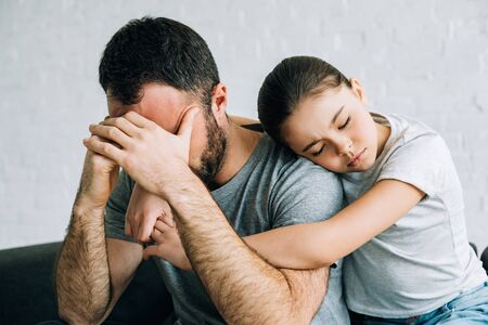 sad kid embracing stressed father in living room