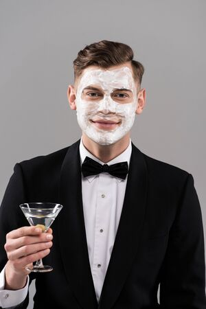 Front view of smiling man in formal wear with cream on face holding glass of cocktail isolated on grey background