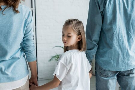 upset kid standing with parents and holding hands at home Stock Photo