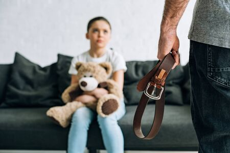 partial view of abusive father holding belt and scared daughter with teddy bear sitting on sofa Stock Photo