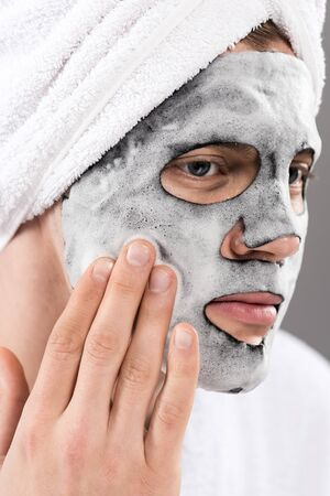 Portrait of man with towel on head with foamy facial mask looking away Stock Photo