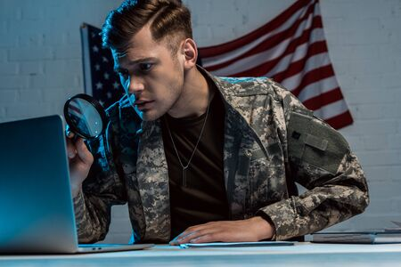 handsome soldier holding magnifying glass near laptop in office