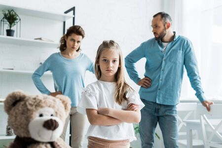 selective focus of cute kid standing with crossed arms near teddy bear and parents at home Stock Photo