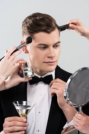 Cropped view of makeup artists doing makeup for man in formal wear holding glass of cocktail isolated on grey background