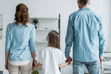 back view of father and mother holding hands of daughter at home Stock Photo