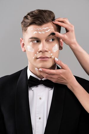 Partial view of cosmetologists applying cream and man in formal wear isolated on grey background