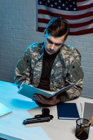 handsome soldier holding folder while sitting in modern office