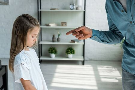 cropped view of man pointing with finger at adorable daughter at home