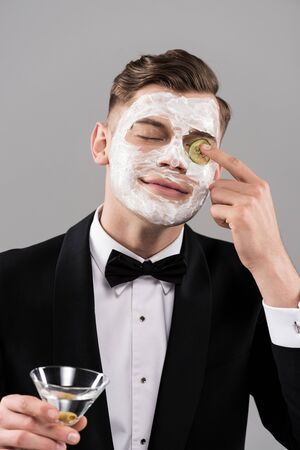 Young man in formal wear with face mask holding glass of cocktail and applying cut cucumber on eye isolated on grey background