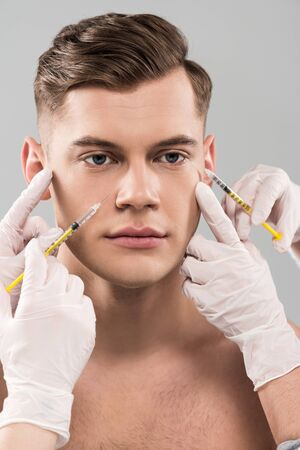 Cropped view of cosmetologists in latex gloves doing beauty injections isolated on grey background