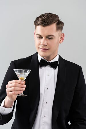 Smiling young man in formal wear with bow tie holding glass of cocktail isolated on grey background 스톡 콘텐츠