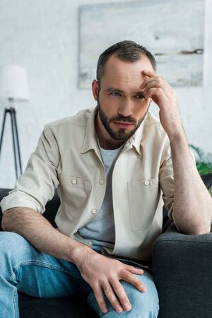 Offended bearded and handsome man touching forehead and sitting on sofa at home Archivio Fotografico - 124712658