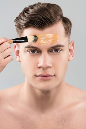 Front view of young man applying facial mask with cosmetic brush isolated on grey background