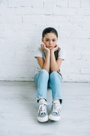 Upset preteen child sitting on floor at home