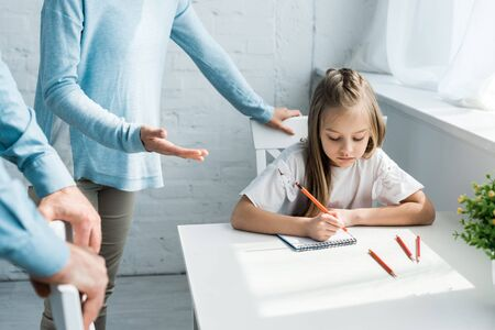 cropped view of parents standing near upset daughter holding pencil at home Stock Photo