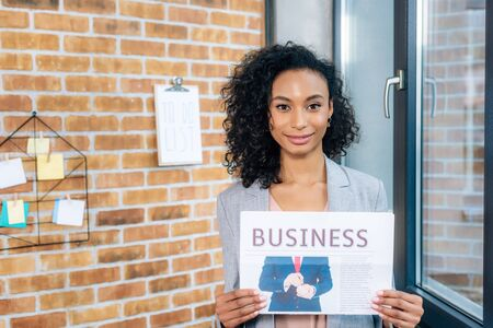 Beautiful African American casual businesswoman holding Business newspaper in loft office